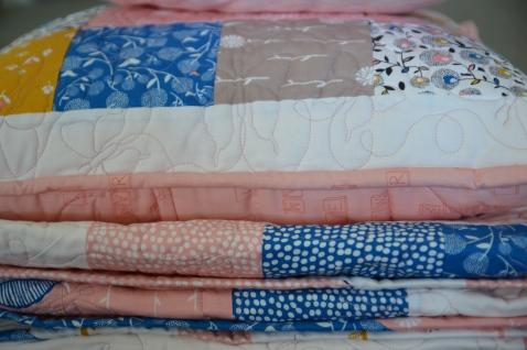 September Blue cushion sitting on folded quilt